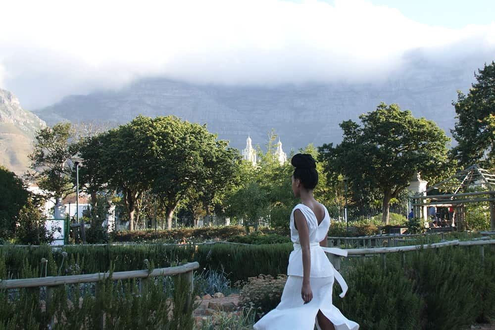 Beautiful African Model walking through a green park in an all white outfit the top is low cut in the back and a ribbon around her waist with an asymmetrical element of a striped pattern on one side and a plain white side, look stunning from the back, flowing in the wind