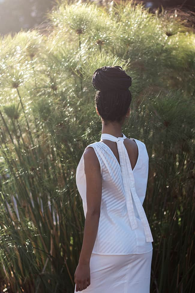 Beautiful African model with dread braids standing at a plant in the park wearing an all white outfit, the top is low cut in the back and a ribbon around the neck with an asymmetrical element of a striped pattern on one side and a plain white side, look stunning from the back