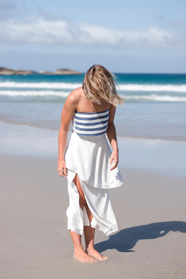 Model standing at the beach in the sun in a top combination of a blue striped bandeau and a flowy top around the waist looking chic
