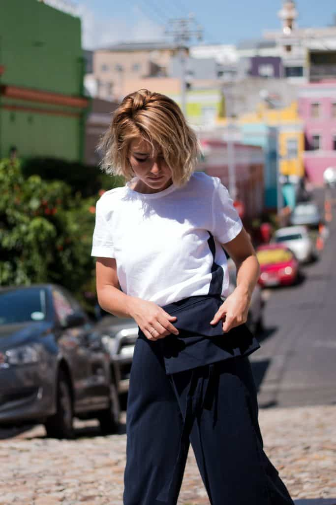 Model walking in a colorful city being fashionable wearing a white linen t-shirt with stripe details on the side and a beltbag with pleats where a mobil phone hast space to fit