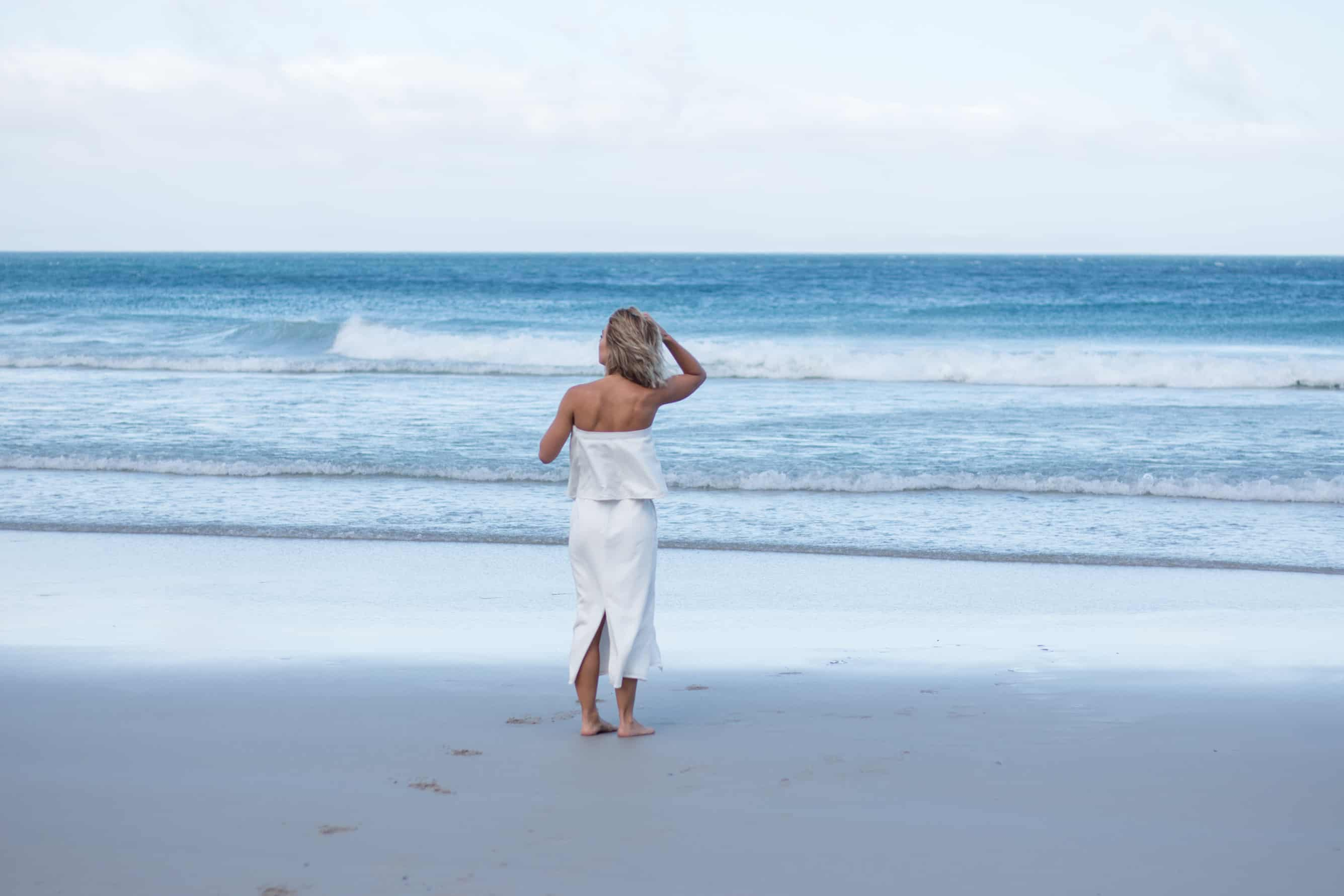 Model dressed in all white clothing looking out to the ocean going through her hair in a beautiful beach look with a white flowy bandeau top and a white skirt