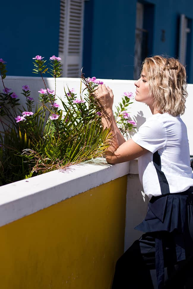 Model leaning on a wall playing with flowers while being fashionable when wearing a white linen t-shirt with stripe details on the side and a beltbag with pleats where a mobile phone hast space to fit