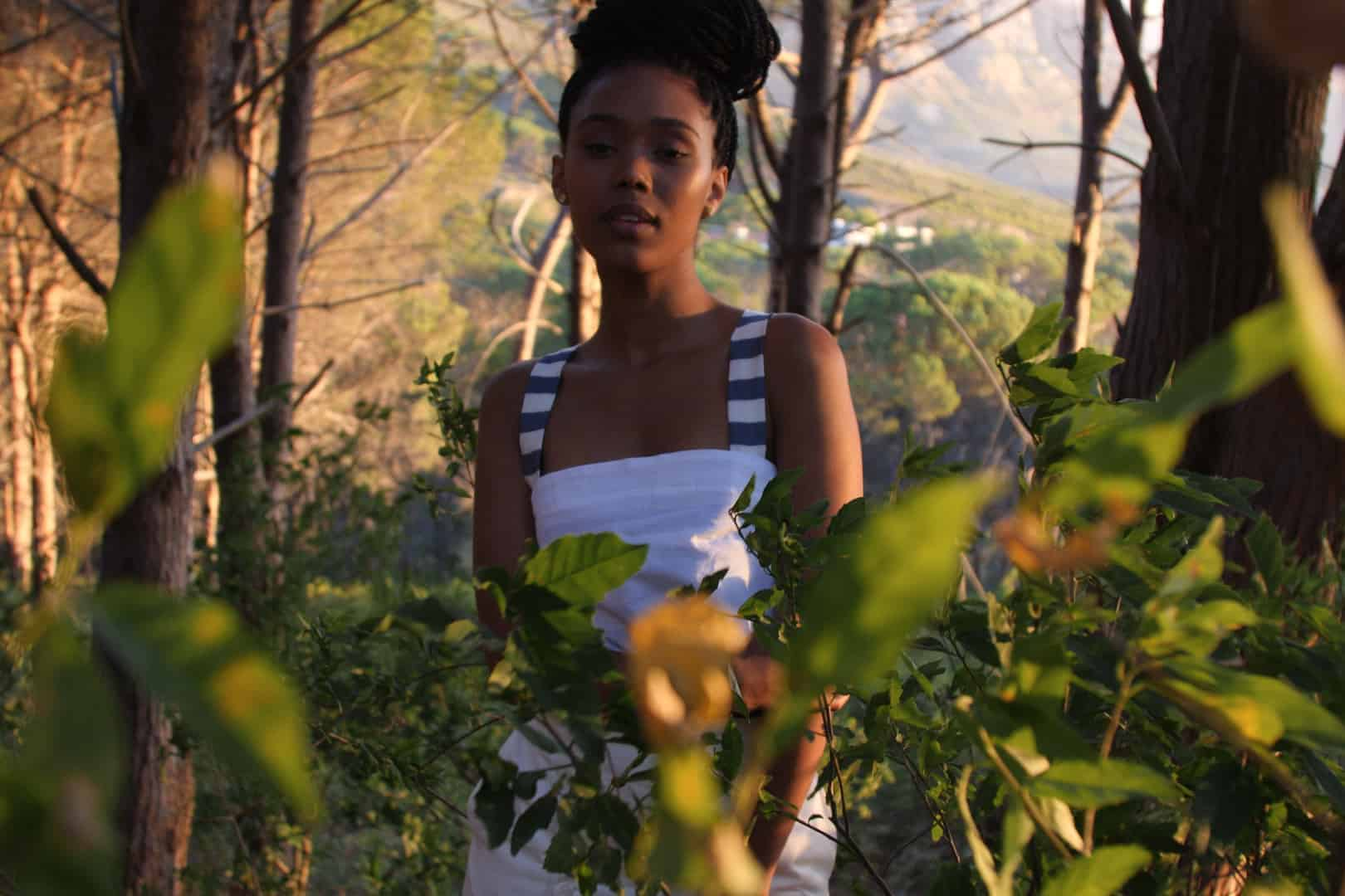 African model with dread braids hairstyle standing in a forest behind trees in the sunset wearing a white bandeau top with striped straps