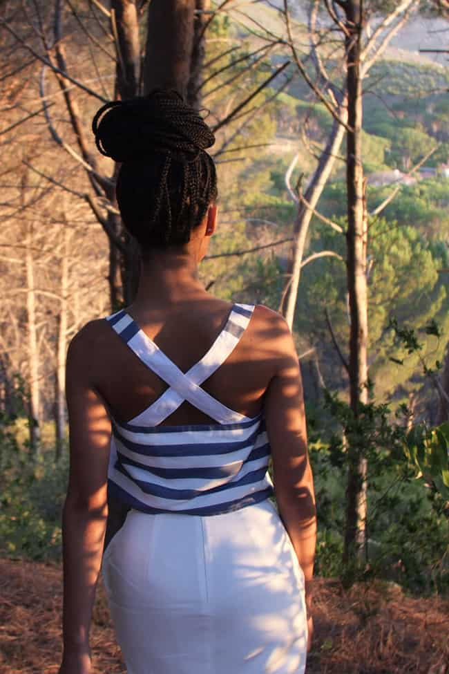 African model with dread braids hairstyle walking in a forest in the sunset wearing a white bandeau top with crossover striped straps