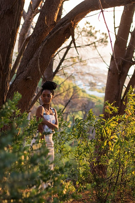 African model with dread braids standing in a forest in the sunset wearing a white bandeau top with striped straps