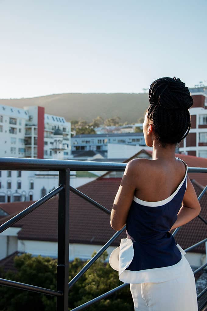 Beautiful African model with dread braids, looking out into the sunset from a balcony wearing a one shoulder sporty dark blue top