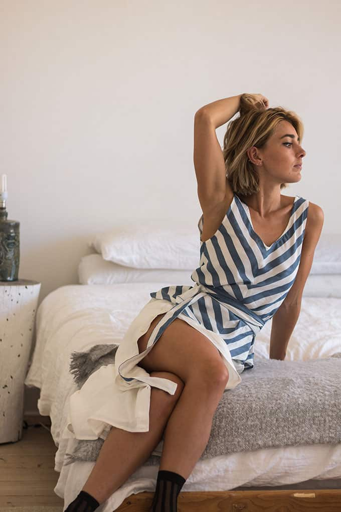 Model in her home sitting on cozy blanket on bed, wearing a striped top with a belt and a white button down skirt combined with striped socks looking trendy