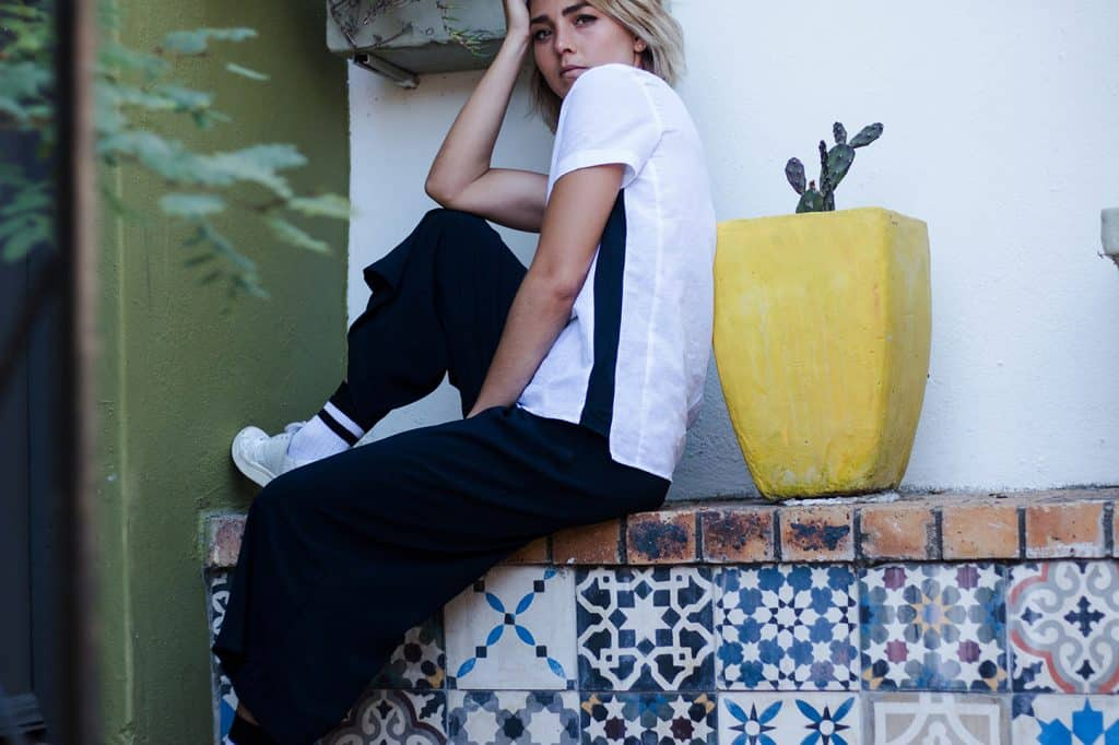 Model sitting on a colorful mosaik wall with a plant pot looking stunning in her white linen t-shirt with a nice stripe detail on the side and an overall sporty styled look
