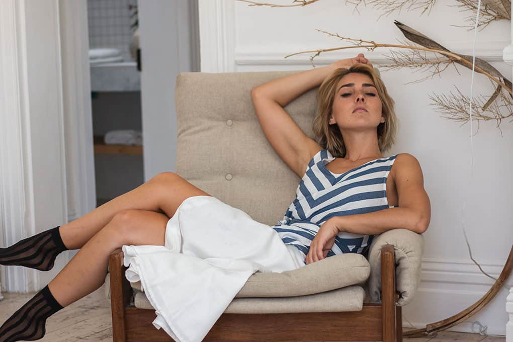 Model is relaxing on an armchair closing her eyes, wearing a striped blue white striped to with a belt with a white button down skirt and black striped stocks