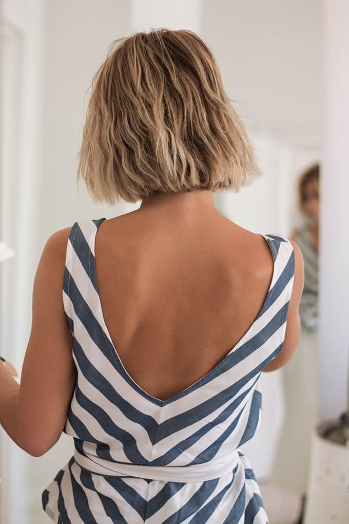 Model in front of the mirror deciding on what to wear while wearing her blue white striped low cut top in the back with a belt